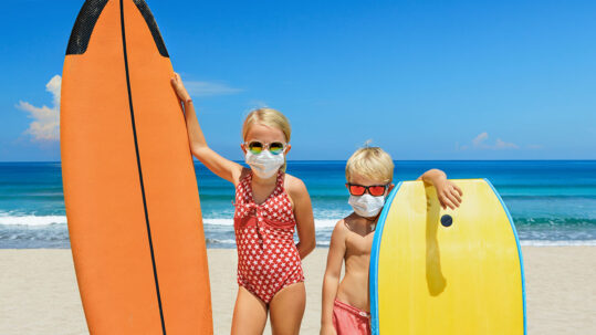 Children on beach with surf boards wearing COVID face masks
